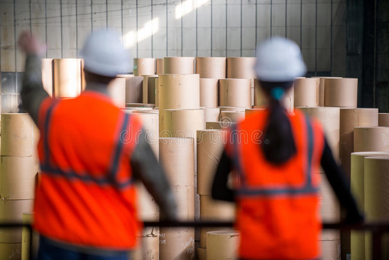 Paper mill factory workers. With giant paper rolls on the background royalty free stock photography