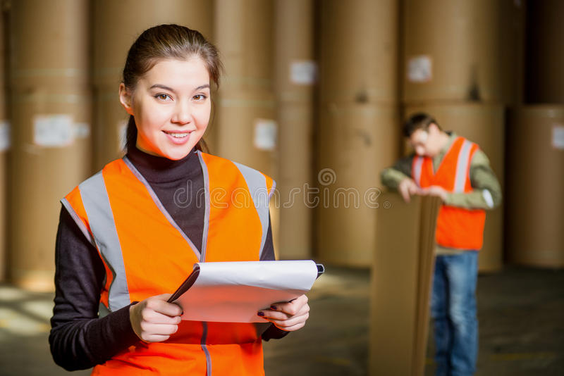 Paper mill factory workers. With giant paper rolls on the background stock image