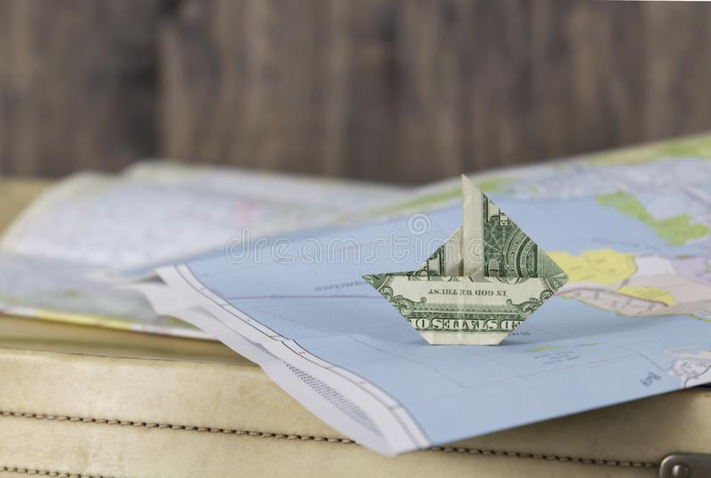 Paper money sailboat on a map royalty free stock photography