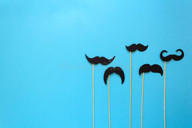 Paper mustache on booth props on blue paper background. Cut out style. Movember concept. Top view. Flat lay. Copy space royalty free stock images