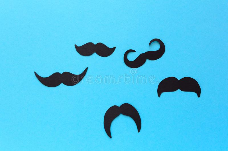 Paper mustache fly like birds to the sun on blue paper background. Cut out style. Movember concept. Top view. Flat lay. Copy space royalty free stock images