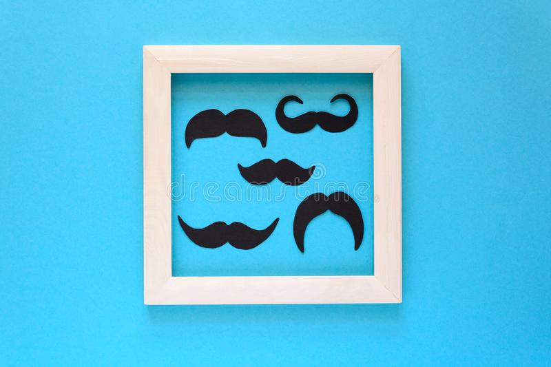 Paper mustache into white wooden frame on blue paper background. Cut out style. Movember concept. Top view. Flat lay. Copy space stock image