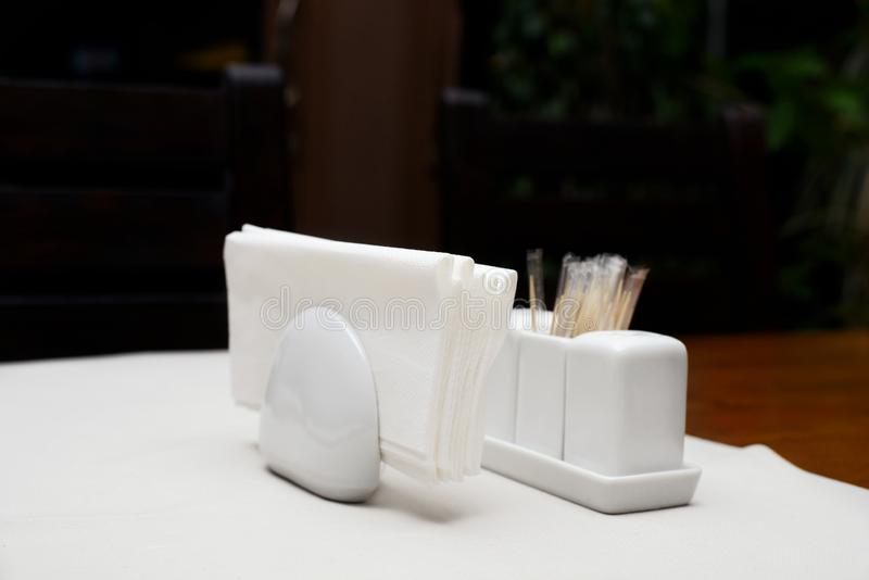 Paper napkins in the holder with salt pepper and toothpicks on table in restaurant on dark background royalty free stock image