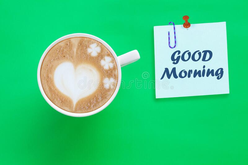 Paper note with good morning text and Hot Coffee Latte Art Heart on background. Paper note with good morning text and Hot Coffee Latte Art Heart on color stock image