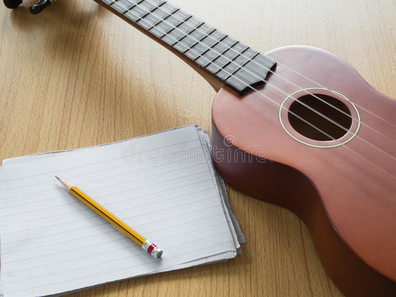 Paper note with Ukulele, Concept for music writing. Paper note with Ukulele, Selective focus on pencil sharpness, Concept for music writing stock image