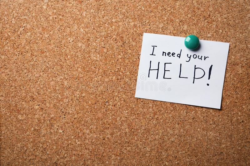 Paper note with words I NEED YOUR HELP on cork board royalty free stock images