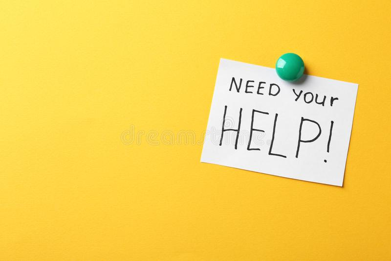 Paper note with words NEED YOUR HELP on color background. stock photography