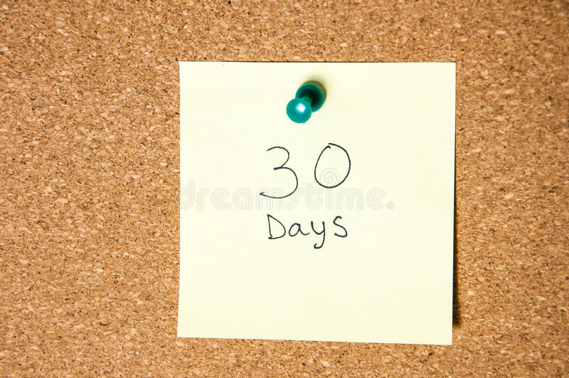Paper note written with 30 DAYS inscription on cork board. stock photography