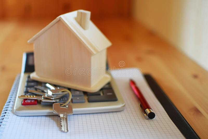 Paper notebook with calculator, house model, keys and pen on wooden table. House building, buying or renting new home planning concept stock photos
