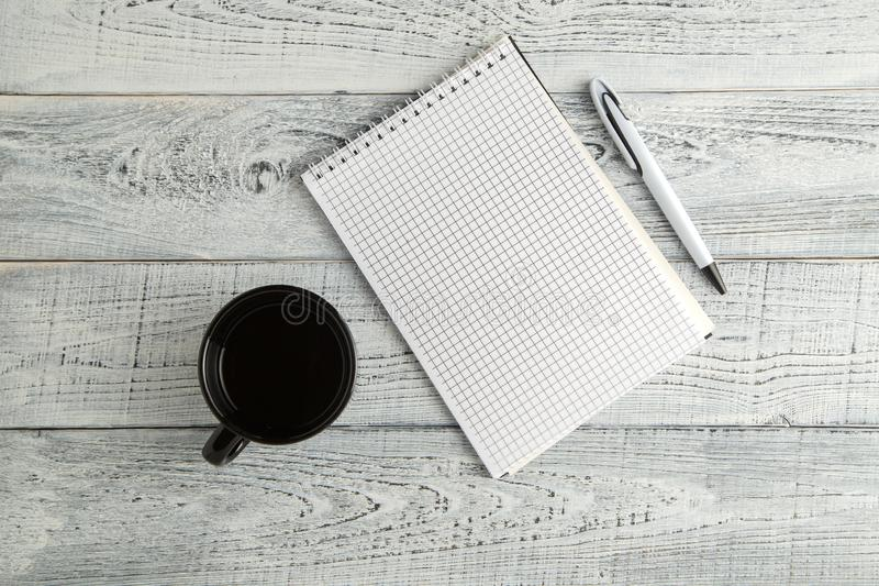 Paper notebook,pen and Cup of tea or coffee on vintage shabby white wooden background. the view from the top. flat lay stock photos