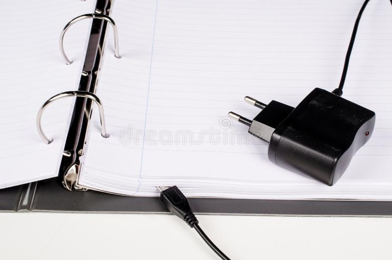 Paper notebook with usb charger royalty free stock photo