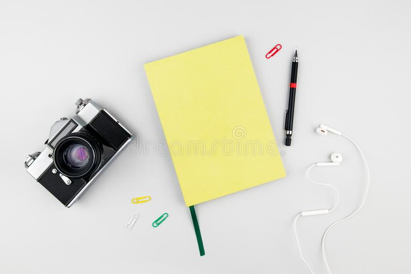 Paper notebook on a white background with vintage camera and office props royalty free stock photography
