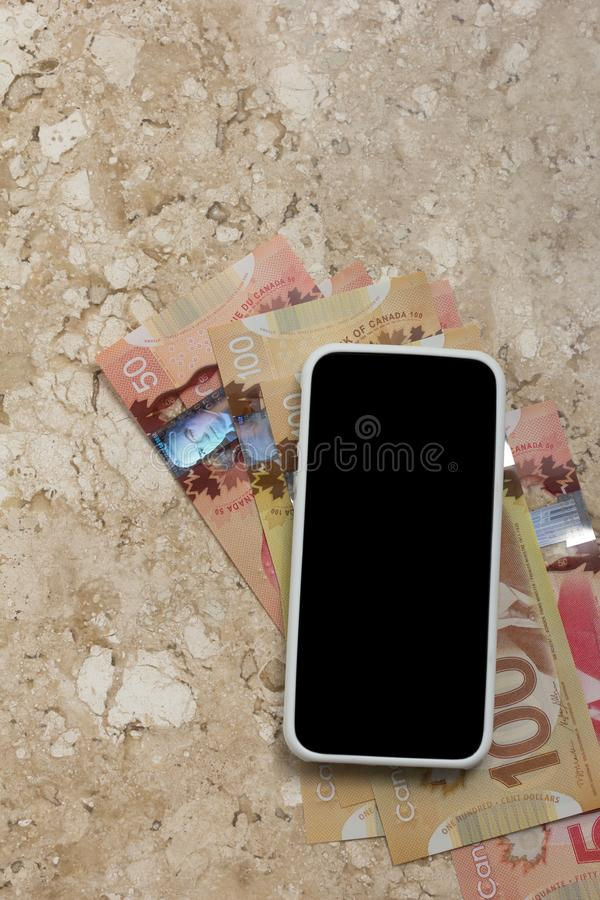Paper notes from Canada. Dollar. Blank cel phone screen and bill stock photo