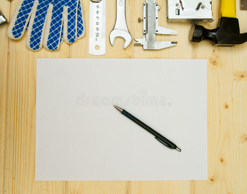 Paper for notes and set of working tools on wooden. Workng tools. Paper for notes and set of working tools (caliper, pliers and others) on wooden background stock images