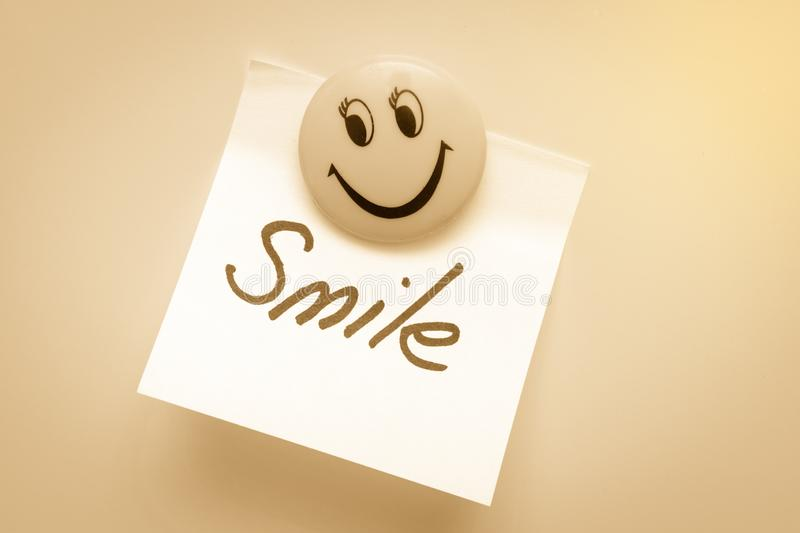 Paper for notes with the word smile on the magnet is toned. stock images