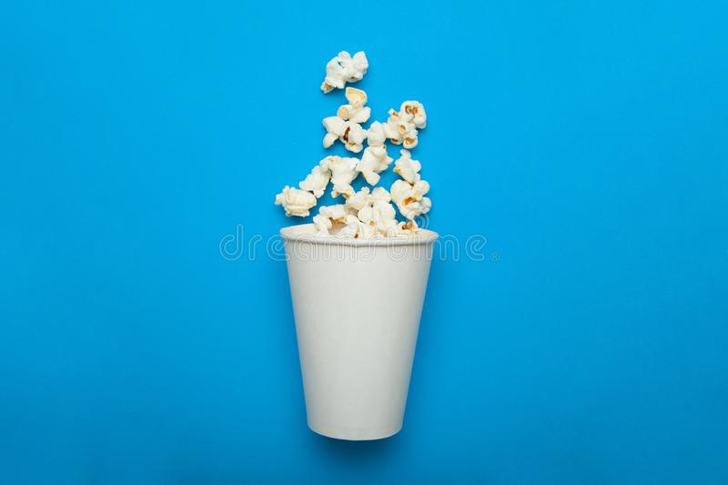 Paper packaging with flying popcorn on a blue background, mock up royalty free stock images