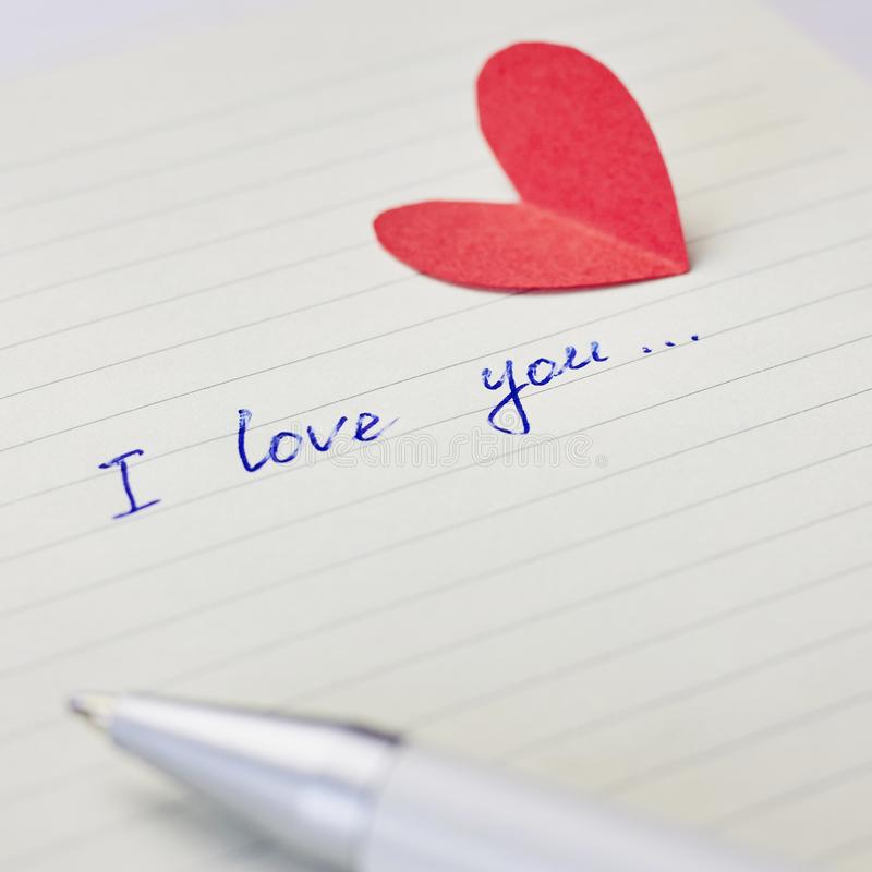 Paper page of notepad with sign I love you, pen and red paper heart. Valentine`s day, wedding, love concept royalty free stock photo