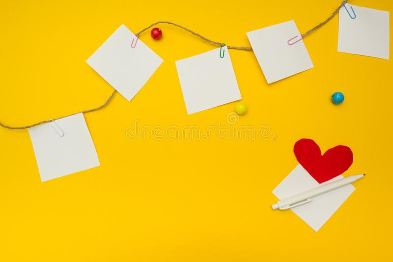 Paper, paper clips, heart and rope on a yellow background, with space for text.  stock images