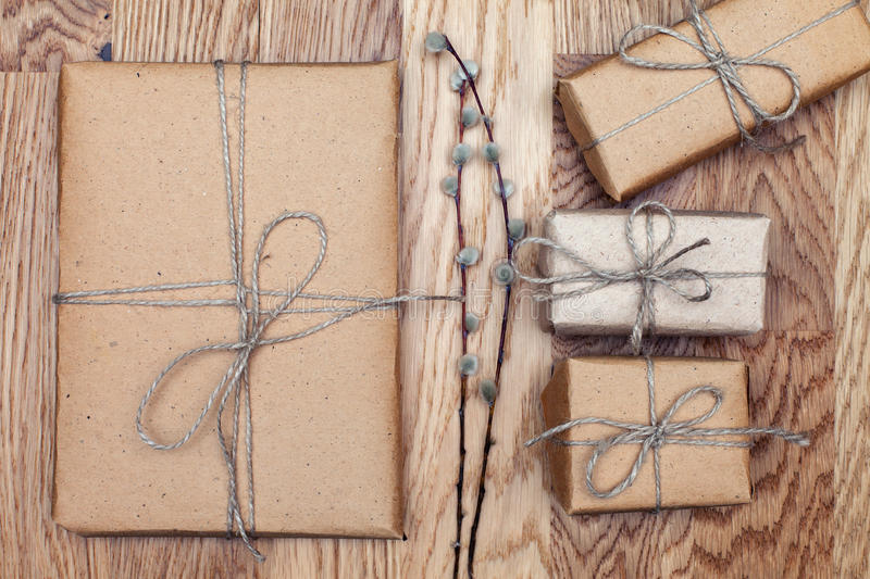 Paper parcels wrapped and tied in kraft paper on a wooden table. Vintage Style. Top view. stock photos
