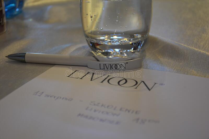 Paper and pen with company logo and glass of water stock images
