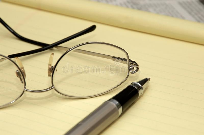 Paper, pen and glasses in an office. A yellow lined legal pad, reading glasses and a ballpoint pen in an office royalty free stock images