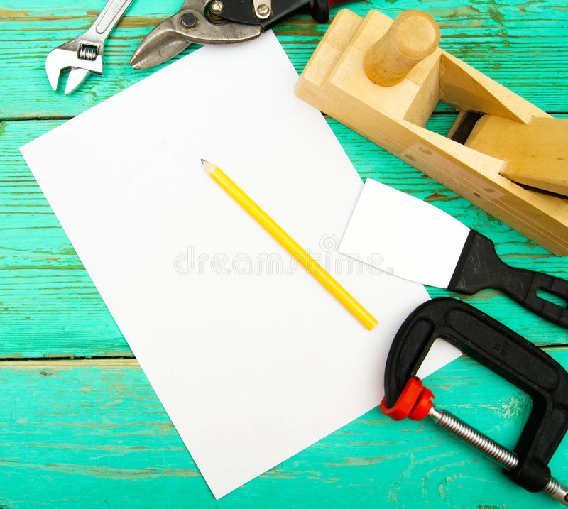 Paper with pencil and the working tool on wooden. Working tools. A paper with pencil and the working tool (Plane, clamp and others) on wooden, green background royalty free stock photos