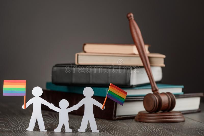 Paper people chain. With LGBT flags before a judge`s gavel. Love and equality celebration, adoption legalisation for gay couple royalty free stock photos