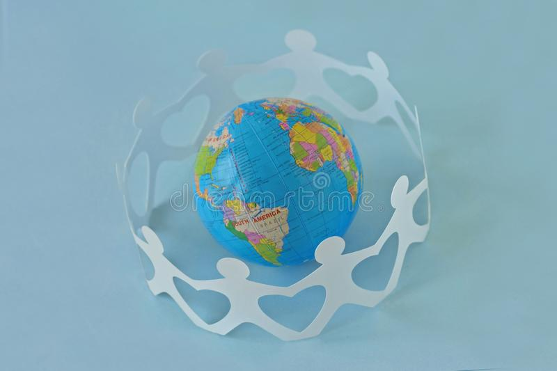 Paper people in a circle around earth globe on blue background -. Love and unity concept stock image