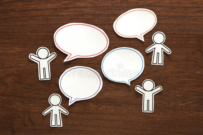 Paper people with colorful blank dialog speech bubbles on brown wood. Communication concept. stock photo