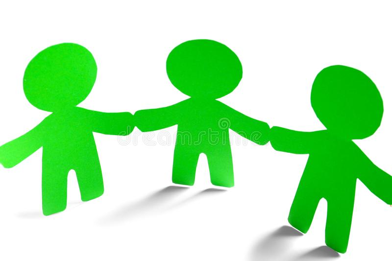 Paper people holding hands on light background stock photo