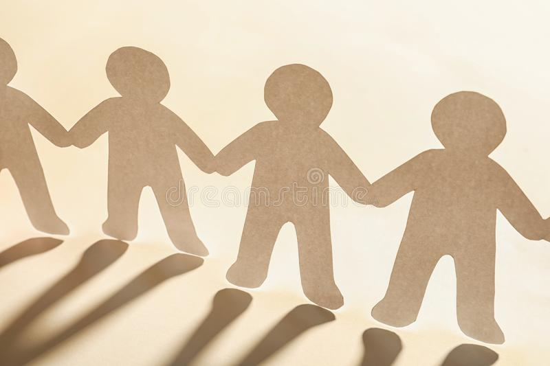Paper people holding hands on light background royalty free stock image