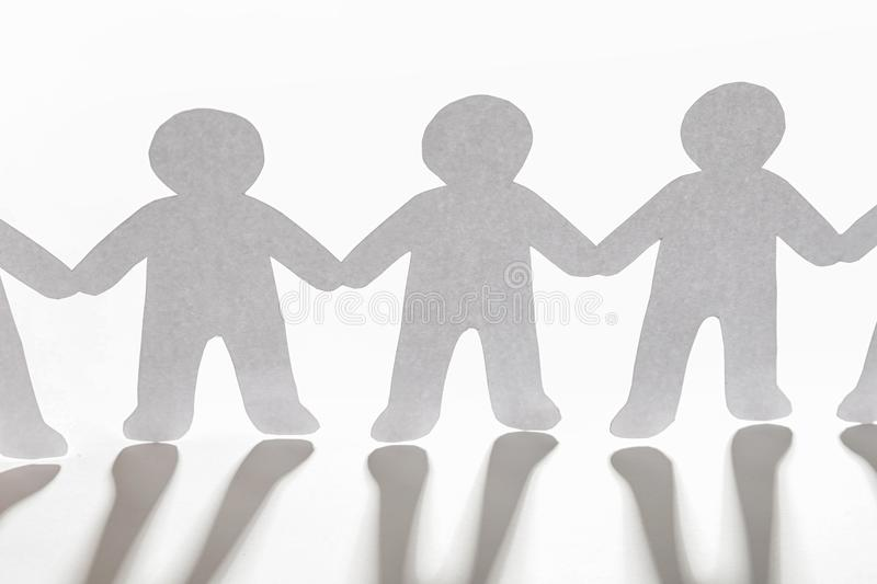 Paper people holding hands on light background royalty free stock photo