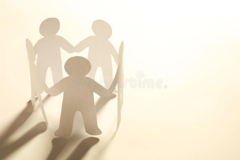 Paper people holding hands on light background. stock photo