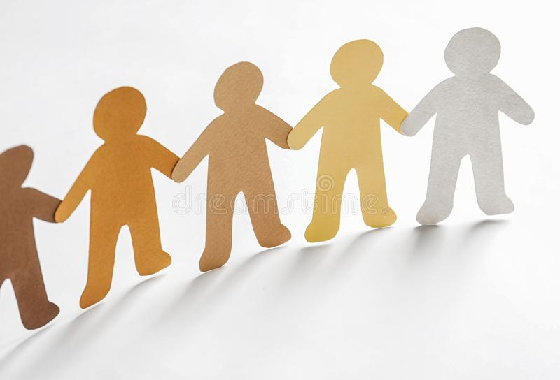 Paper people holding hands on light background stock images