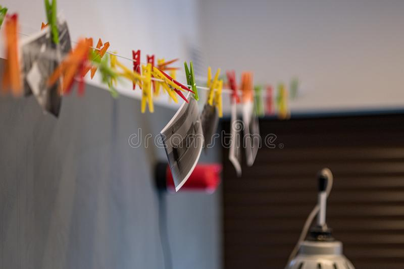 Paper photograph drying wire with hooks in analog darkroom. With red safelight stock photo