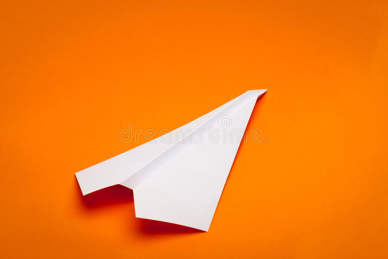 Paper plane. White paper plane on orage paper background stock photo