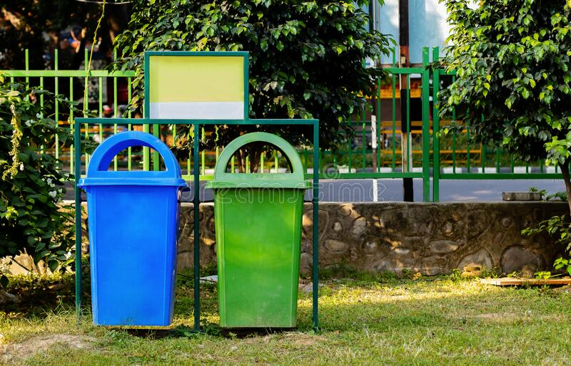 Paper and plastic recycle bin placed in the garden for cleanness. cleanness concept royalty free stock photos