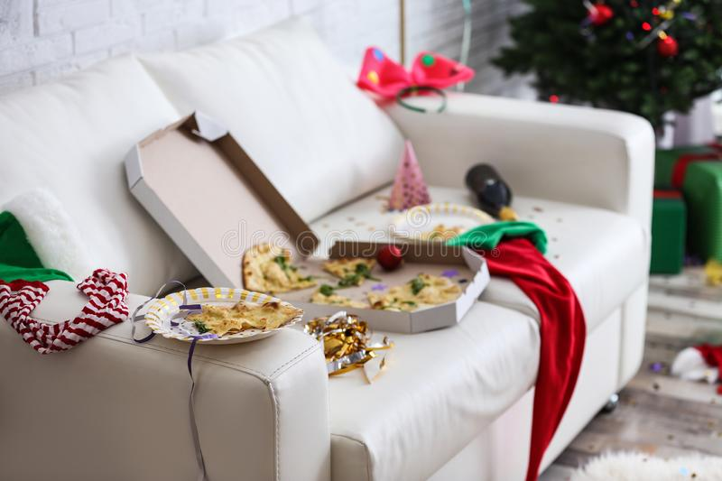 Paper plate with piece of pizza on messy sofa. Chaos after party royalty free stock photography