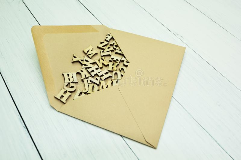 Paper postal envelope with wooden letters inside on a white table royalty free stock image