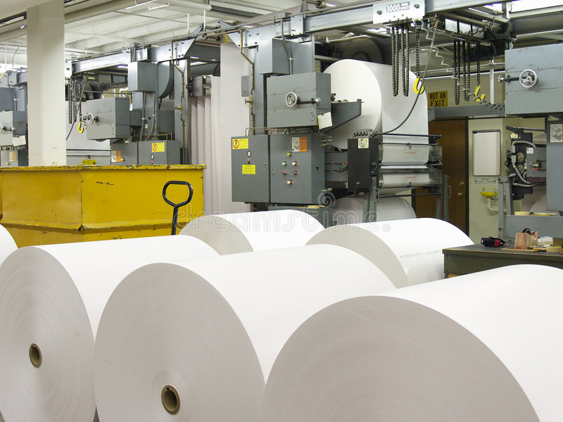 Paper and Press. Paper rolls in front of printing press stock photos