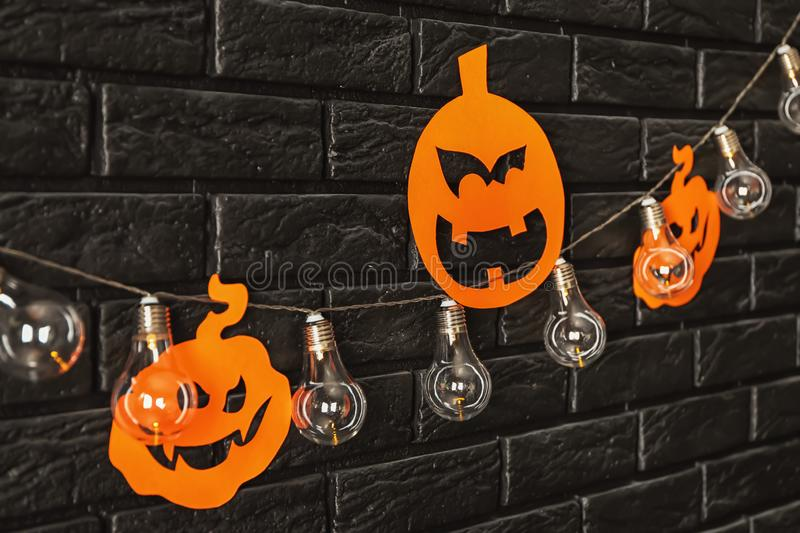 Paper pumpkins with garland as decor for Halloween party on dark brick wall stock photos