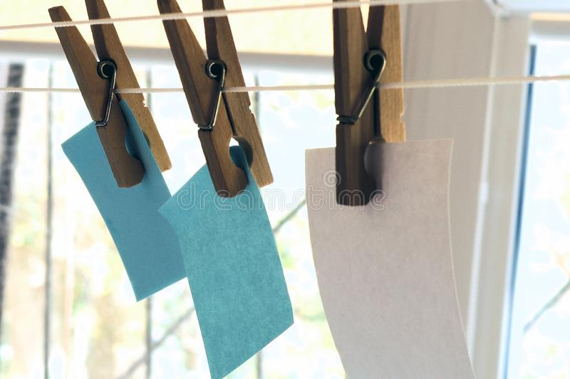 Paper for records on a clothesline attached with wooden clothespins, white paper sheets for notes royalty free stock photography