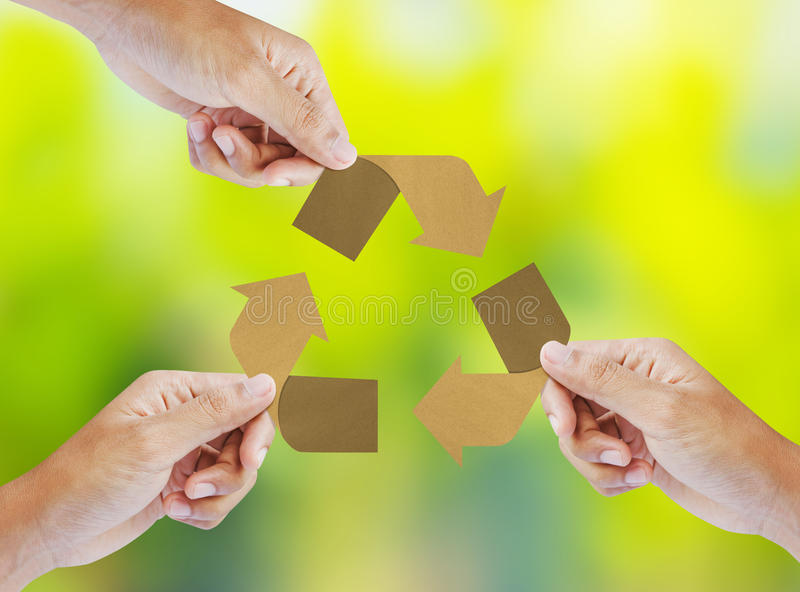 Paper recycle sign in hands. On green background royalty free stock image
