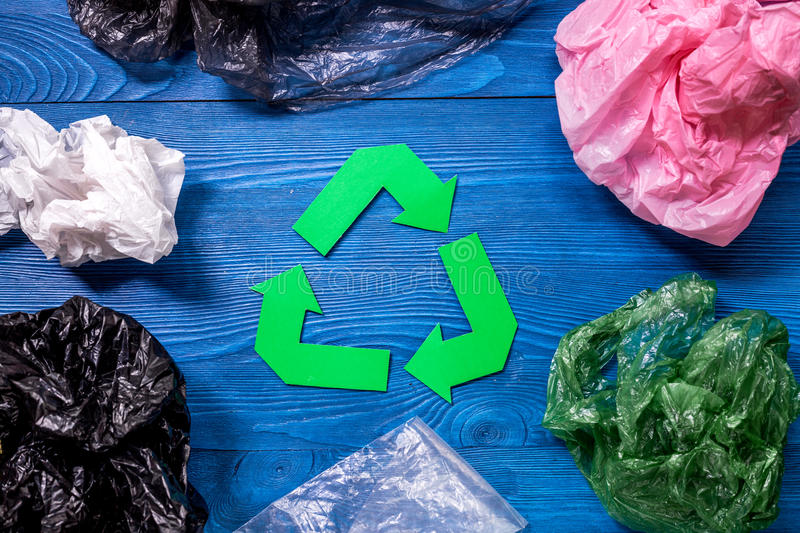Paper recycle sign with plastic garbage on blue wooden background top view.  stock image