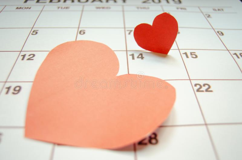 Paper red hearts marking 14 february Valentines day on white calendar royalty free stock image