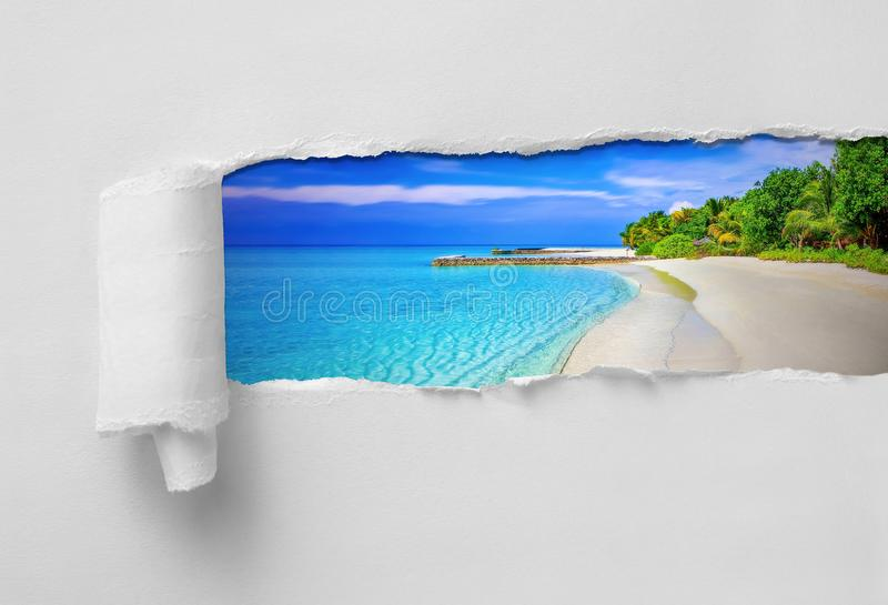 Paper Ripped revealing paradisiac tropical sea and beach. Vacation destination royalty free stock photo