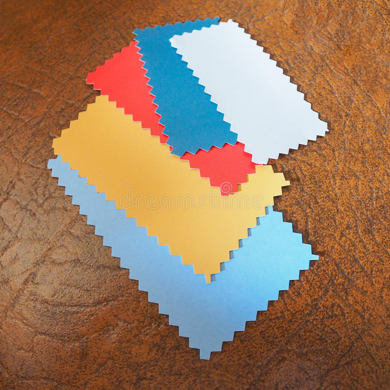 Paper sample. Colour paper swatches with zig zag border cut with pinking shears on a leatherette background royalty free stock images