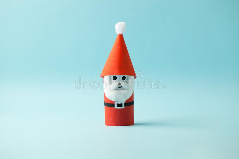 Paper Santa Claus for Happy new year Merry Christmas party. Easy craft for kids on blue background, simple diy idea from toilet. Rool tube, recycle concept stock photos