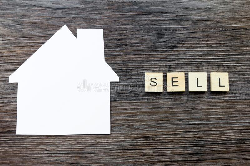 Paper in the shape of a house and the word `sell`. House Selling Concept - Paper house with the word `Sell stock photography