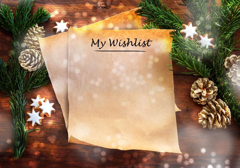 Paper sheet with text My Wishlist between fir branches, cinnamon stars and Christmas decoration on rustic dark wood, wish list or. Letter to Santa Claus with royalty free stock photography